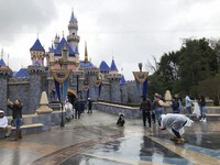 In this March 13, 2020, file photo, visitors take photos at Disneyland in Anaheim, Calif. California officials will allow people to attend Major League Baseball games and other sporting events, go to Disneyland and watch live performances in limited capacities starting April 1, 2021. (AP Photo/Amy Taxin)