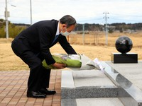 Prime Minister Yoshihide Suga offers flowers at a monument dedicated to the victims of the March 11, 2011 Great East Japan Earthquake, in Namie, Fukushima, on March 6, 2021. (Pool photo)
