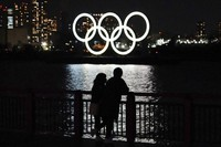 A man and a woman stand with the backdrop of the Olympic rings floating in the water in the Odaiba area of Tokyo, on March 3, 2021. (AP Photo/Eugene Hoshiko)