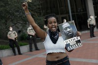 In this Thursday, May 28, 2020, file photo, a protester holds a photo of George Floyd during a protest at the Hennepin County Government Center, as protests continue over the death of Floyd, who died in police custody Monday night in Minneapolis, after video shared online by a bystander showed a white officer kneeling on his neck during his arrest as he pleaded that he couldn't breathe. (AP Photo/Jim Mone, File)