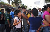 In this July 31, 2019 file photo, migrants line up in Matamoros, Mexico, for a meal donated by volunteers from the U.S., at the foot of the Puerta Mexico bridge that crosses to Brownsville, Texas. (AP Photo/Emilio Espejel, File)