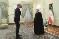 In this photo released by the official website of the office of the Iranian Presidency, President Hassan Rouhani, right, and Irish Foreign Minister Simon Coveney greet at the start of their meeting in Tehran, Iran, Sunday, March 7, 2021. (Iranian Presidency Office via AP)