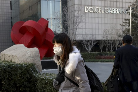 In this Nov. 25, 2018 file photo, a woman walks past a Dolce&Gabbana retail outlet in Beijing, China. (AP Photo/Ng Han Guan, file)