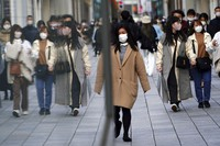 People wearing protective masks to help curb the spread of the coronavirus walk on a street Monday, March 1, 2021, in Tokyo. (AP Photo/Eugene Hoshiko)