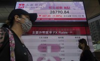 People walk past a bank's electronic board showing the Hong Kong share index at the Hong Kong Stock Exchange in Hong Kong, on March 8, 2021. (AP Photo/Vincent Yu)