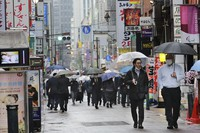 People wearing face masks walk on a street lined with bars and restaurants in Tokyo on March 8, 2021. (AP Photo/Koji Sasahara)