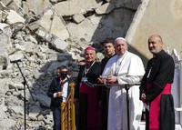 Pope Francis, surrounded by shells of destroyed churches, attends a prayer for the victims of war with Mosul and Aqra Archbishop Najib Mikhael Moussa, left, at Hosh al-Bieaa Church Square, in Mosul, Iraq, once the de-facto capital of IS, on March 7, 2021. (AP Photo/Andrew Medichini)