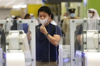 A Japanese journalist checks out the new face and iris-recognition procedures, during a media tour at Dubai airport, United Arab Emirates, on March 7, 2021. (AP Photo/Kamran Jebreili)