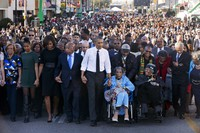 """In this March 7, 2015, file photo, President Barack Obama, center, walks as he holds hands with Amelia Boynton Robinson, who was beaten during """"Bloody Sunday,"""" as the first family and others including Rep. John Lewis, D-Ga., left of Obama, walk across the Edmund Pettus Bridge in Selma, Ala., for the 50th anniversary of """"Bloody Sunday,"""" a landmark event of the civil rights movement. From front left are Marian Robinson, Sasha Obama, first lady Michelle Obama, Obama, Boynton and Adelaide Sanford, also in wheelchair. (AP Photo/Jacquelyn Martin)"""
