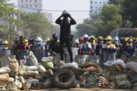 Protesters take positions behind a barricade as police gather in Yangon, Myanmar, on March 7, 2021. (AP Photo)