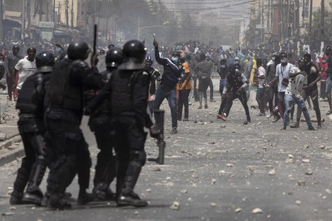Demonstrators throw rocks at riot policemen during protests against the arrest of opposition leader and former presidential candidate Ousmane Sonko in Dakar, Senegal, on March 5, 2021. (AP Photo/Leo Correa)