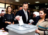 This April 13, 2016 file photo released on the official Facebook page of Syrian Presidency, shows Syrian President Bashar Assad casting his ballot in the parliamentary elections, as his wife Asma, left, stands next to him, in Damascus, Syria. (Syrian Presidency via AP)