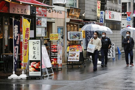 People wearing face masks to protect against the spread of the coronavirus walk on an almost empty street lined with bars and restaurants in Tokyo, on March 8, 2021. (AP Photo/Koji Sasahara)