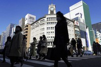 People wearing protective masks to help curb the spread of the coronavirus walk along a pedestrian crossing in Tokyo, on March 3, 2021. (AP Photo/Eugene Hoshiko)