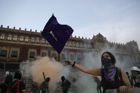 A woman waves a feminist flag as demonstrators attempt to storm the National Palace during a march to commemorate International Women's Day and protesting against gender violence, in Mexico City, on March 8, 2021. (AP Photo/Rebecca Blackwell)