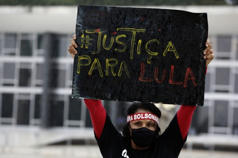 """A demonstrator wearing a mask to curb the spread of the new coronavirus and wearing a headband with text in Portuguese that reads """"Bolsonaro out"""" raises a sign that reads """"Justice for Lula,"""" in reference to former Brazilian President Luiz Inacio Lula da Silva, during a protest commemorating the Supreme Court's decision to suspend proceedings against Lula, in front of the Supreme Court building in Brasilia, Brazil, on March 8, 2021. (AP Photo/Eraldo Peres)"""