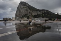People cross the Gibraltar airport runway towards the border crossing with Spain, backdropped by the Gibraltar rock, in Gibraltar, on March 5, 2021. (AP Photo/Bernat Armangue)