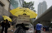 A supporter holds an umbrella and a placard outside a court in Hong Kong on March 4, 2021. (AP Photo/Vincent Yu)