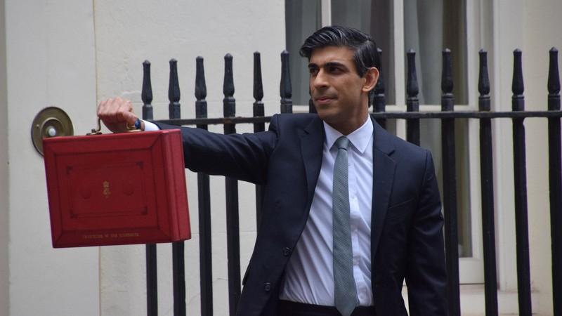 予算案の入った赤い箱を手に報道陣の前に登場した英国のスナク財務相=ロンドンで2021年3月3日、横山三加子撮影