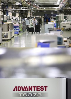 アドバンテストのテスター工場(群馬県邑楽町)と同社ロゴ(下)(Bloomberg)