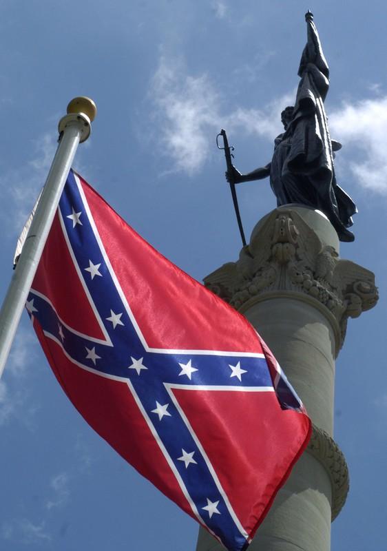 アラバマ州モンゴメリーの州議会議事堂の敷地内にある内戦記念碑の隣に南軍の旗が掲げられている(Bloomberg)