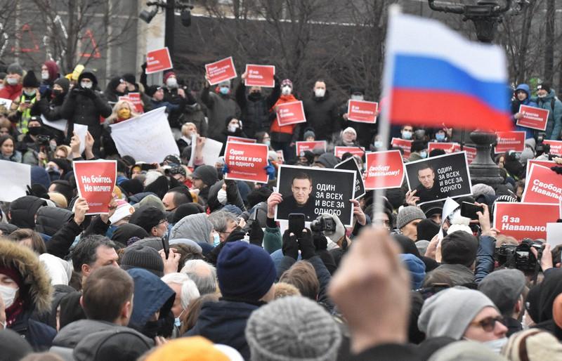 反体制派指導者アレクセイ・ナワリヌイ氏の写真を掲げ、プーチン政権を批判する抗議集会の参加者=ロシア・モスクワ中心部のプーシキン広場で2021年1月23日、前谷宏撮影