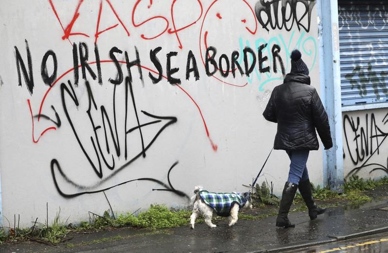 「アイリッシュ海の境界にノー」と書かれた壁の前を通り過ぎる女性=北アイルランドのベルファストで2021年2月3日、AP