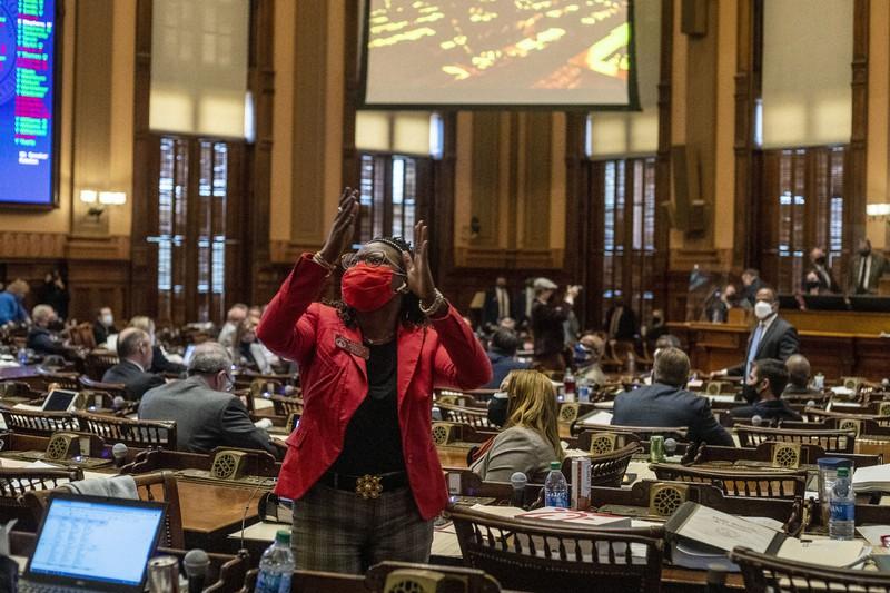 米南部ジョージア州議会で、改正投票法案に反対する同僚議員の演説に拍手を送る民主党のパーク・キャノン議員=3月25日、AP
