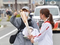 An official staff member reignites the Olympic torch after its flame went out during the torch relay in Tomioka, Fukushima Prefecture, on March 25, 2021. (Pool photo)