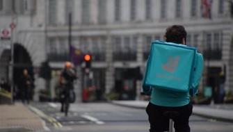 英国の街中を自転車で走るデリバルーの配達員=ロンドンで2021年4月1日、横山三加子撮影