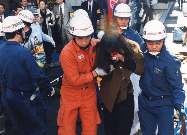地下鉄サリン事件。ハンカチなどで口を押さえながら、レスキュー隊員らに救出された被害者=1995年3月20日撮影