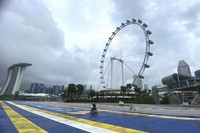 Cyclists pass by the Singapore Flyer Ferris Wheel attraction in Singapore on March 7, 2021. (AP Photo/Annabelle Liang)
