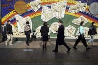 People wearing protective masks walk in Tokyo's Shibuya district on April 7, 2021. (AP Photo/Eugene Hoshiko)