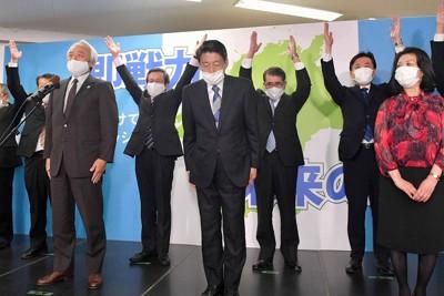 当選確実となり、支持者らの万歳を受けて頭を下げる服部誠太郎氏(中央)=福岡市博多区で2021年4月11日午後8時7分、平川義之撮影