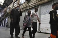People walk through closed Tehran's Grand Bazaar, Iran, Saturday, April 10, 2021. (AP Photo/Vahid Salemi)