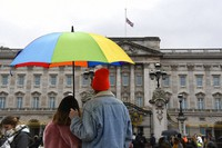 A couple under an umbrella look at the Union flag at half-staff over Buckingham Palace in London, a day after the death of Britain's Prince Philip, Saturday, April 10, 2021. (AP Photo/Alberto Pezzali)