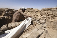 A man cover a skeleton in a 3,000-year-old lost city in Luxor province, Egypt, Saturday, April 10, 2021. (AP Photo/Mohamed Elshahed)