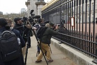 In this Friday, April 9, 2021 file photo, members of the media take images of an announcement, regarding the death of Britain's Prince Philip, displayed on the fence of Buckingham Palace in London. (AP Photo/Matt Dunham, File)