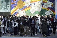 People wearing protective masks to help curb the spread of the coronavirus walk along a pedestrian crossing in Shibuya district in Tokyo on April 7, 2021. (AP Photo/Eugene Hoshiko)