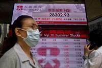 People walk past a bank's electronic board showing the Hong Kong share index at Hong Kong Stock Exchange in Hong Kong on April 12, 2021. (AP Photo/Vincent Yu)