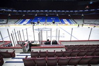 Off-ice officials pack up equipment after the Vancouver Canucks and Calgary Flames NHL hockey game was postponed due to a positive COVID-19 test result in Vancouver, British Columbia, on March 31, 2021. (Darryl Dyck/The Canadian Press via AP)
