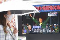 People walk past the tv screen showing the image of Japanese golfer Hideki Matsuyama in a news channel in Tokyo, on April 12, 2021. (AP Photo/Koji Sasahara)