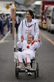 Shigeko Kagawa, the torch bearer for the Olympic flame relay's fifth section of the second day in Nara Prefecture, is seen with the torch mounted on a wheelchair in the city of Yamatokoriyama, on April 12, 2021. (Pool photo)