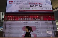 A woman wearing a face mask walks past a bank's electronic board showing the Hong Kong share index at Hong Kong Stock Exchange in Hong Kong on April 13, 2021. (AP Photo/Vincent Yu)