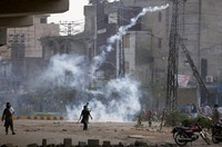 An angry supporter of Tehreek-e-Labiak Pakistan, a radical Islamist political party, hurls back a tear gas shell fired by police to disperse them, at a protest against the arrest of their leader Saad Rizvi, in Lahore, Pakistan, on April 12, 2021. (AP Photo/K.M. Chaudary)