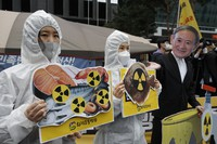 Environmental activists wearing a mask of Japanese Prime Minister Yoshihide Suga and protective suits perform to denounce the Japanese government's decision on Fukushima water, near the Japanese embassy in Seoul, South Korea, on April 13, 2021. (AP Photo/Lee Jin-man)