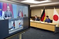 """Japanese Foreign Minister Toshimitsu Motegi, second from right, and Defense Minister Nobuo Kishi, right, attend a video conference with German Foreign Minister Heiko Maas, top left on screen, and German Defense Minister Annegret Kramp-Karrenbauer, top right on screen, at Foreign Ministry in Tokyo during their """"2 plus 2"""" ministerial meeting on April 13, 2021. (Frank Robichon/Pool Photo via AP)"""