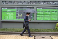 A man walks by an electronic stock board of a securities firm in Tokyo on April 14, 2021. (AP Photo/Koji Sasahara)