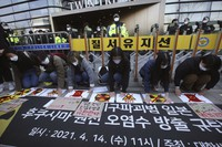 Environmental activists attach stickers on a street during a rally to denounce the Japanese government's decision on Fukushima water, in front of a building which houses the Japanese embassy in Seoul, South Korea, on April 14, 2021. (AP Photo/Ahn Young-joon)