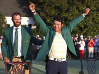 Hideki Matsuyama, of Japan, celebrates while wearing the champion's green jacket as Dustin Johnson looks on after winning the Masters golf tournament on April 11, 2021, in Augusta, Ga. (Curtis Compton/Atlanta Journal-Constitution via AP)